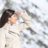 Woman looking forward with the hand on forehead in winter holidays with a snowy mountain in the background